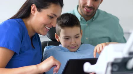 stomatological : dentist showing tablet pc to kid at dental clinic
