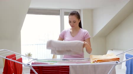 сложить : woman taking bath towels from drying rack at home