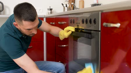 forno : man with rag cleaning oven door at home kitchen