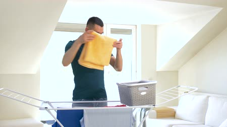 linen : man taking laundry from drying rack at home Stock Footage