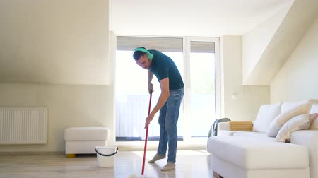 servant : man in headphones cleaning floor by mop at home