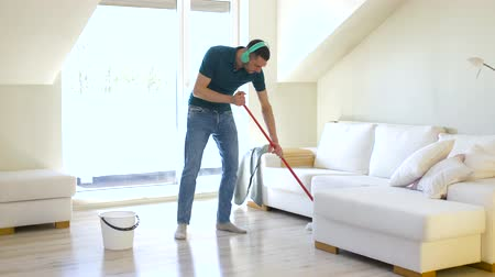 swabber : man in headphones cleaning floor by mop at home