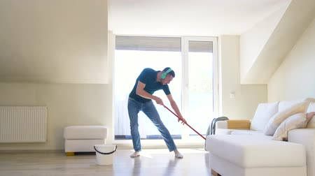 playlist : man in headphones cleaning floor by mop at home