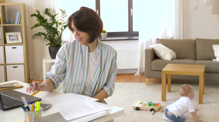 bookkeeping : working mother with baby boy at home office Stock Footage