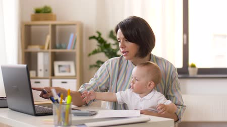 reszelő : working mother with baby boy at home office Stock mozgókép