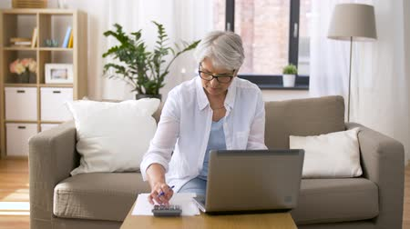 входящий : senior woman with laptop and calculator at home Стоковые видеозаписи
