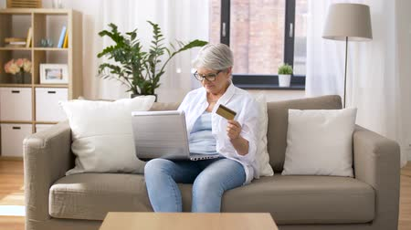 cash free : senior woman with laptop and credit card at home Stock Footage