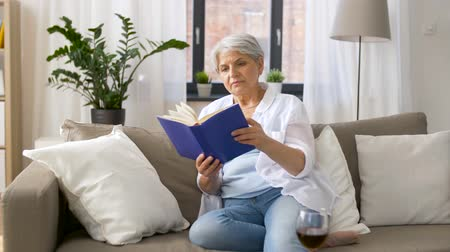 red wine : senior woman reading book at home