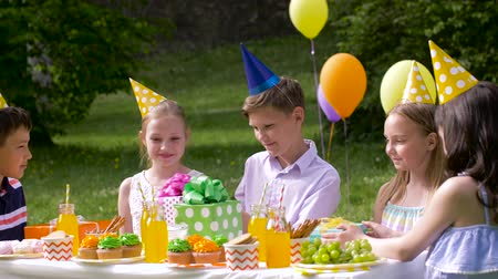 vendég : kids giving presents to birthday child at party