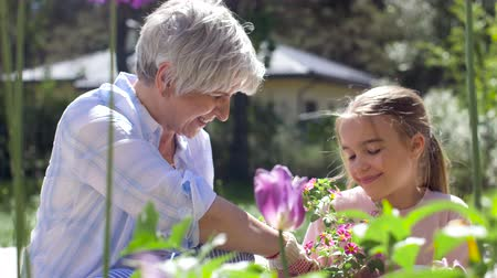 пригородный : grandmother and girl planting flowers at garden