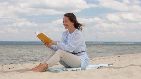 boho : happy smiling woman reading book on summer beach Stock Footage