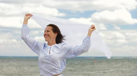 boho : happy woman with shawl waving in wind on beach