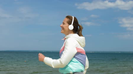 playlist : smiling woman with headphones running along beach