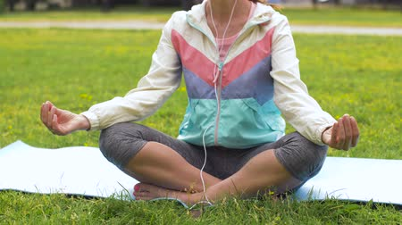 tunes : woman with earphones meditating at park