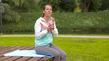 sports nutrition : woman drinking smoothie after exercising in park