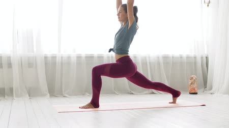 testtartás : woman making high lunge exercise at yoga studio