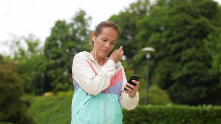 playlist : woman running at park with music on smartphone Stock Footage
