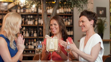bachelorette party : women giving present to friend at wine bar