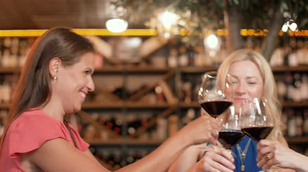 три человека : happy women drinking red wine at bar or restaurant