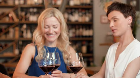bachelorette party : happy women drinking red wine at bar or restaurant