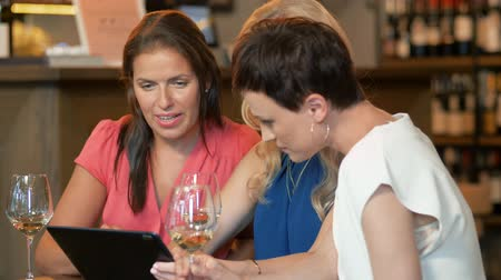 bachelorette party : women with tablet pc at bar wine or restaurant
