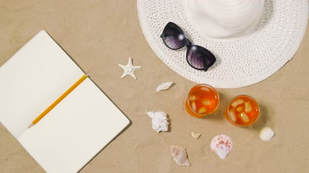 kalap : notebook, cocktails, hat and shades on beach sand