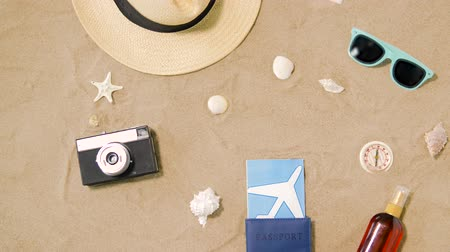 kalap : travel tickets, camera and hat on beach sand