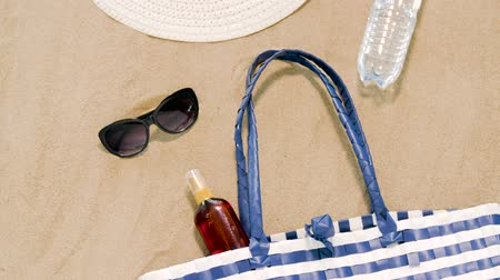 kalap : beach bag, sunscreen, sunglasses and hat on sand