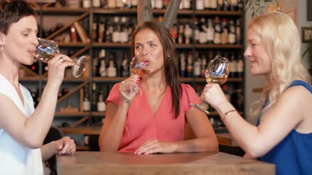 bachelorette party : happy women drinking wine at bar or restaurant