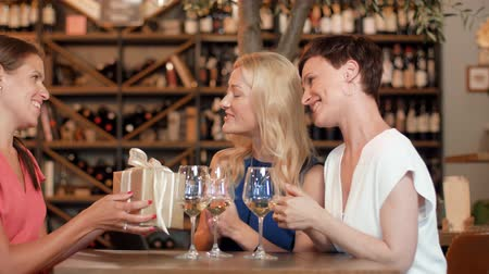 congratulating : women giving present to friend at wine bar