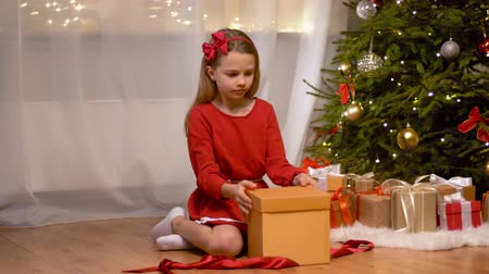x mas : happy girl opening christmas gift at home