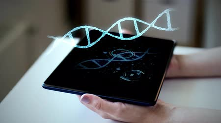 genoma : mani con tablet pc e ologramma virtuale di dna Filmati Stock
