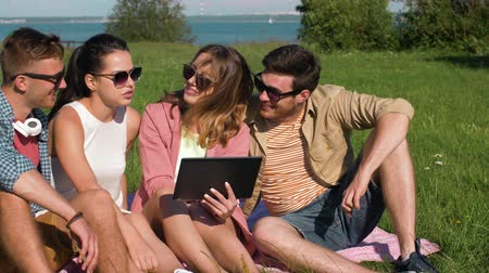 estonia : smiling friends with tablet pc sitting on grass