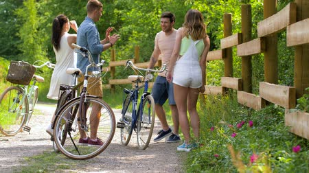 hispánský : happy friends with bicycles dancing at summer park
