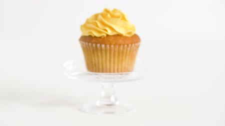 cukros : cupcake with yellow frosting on glass stand