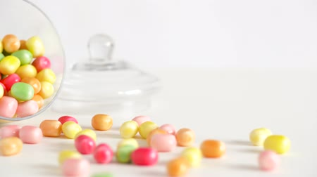 cukros : close up of scattered candy drops and jar on table Stock mozgókép