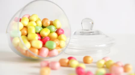 dragee : close up of scattered candy drops and jar on table Stock Footage