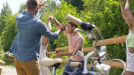 tendo : happy friends with bicycles dancing at summer park