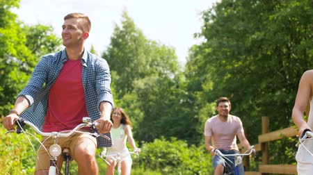 adult woman : happy friends riding fixed gear bicycles in summer