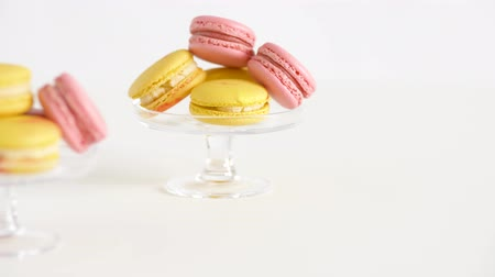 разница : yellow and pink macarons on glass stands Стоковые видеозаписи