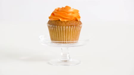 углеводы : cupcake with orange frosting on glass stand Стоковые видеозаписи