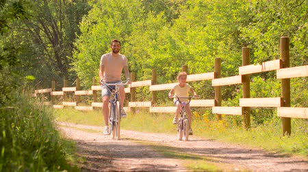 pre hispanic : father and daughter riding bicycles in summer park Stock Footage