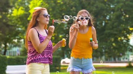 boho : teenage girls blowing bubbles in summer park