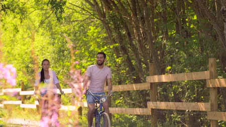 пригородный : happy couple riding bicycles at summer park