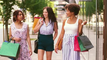 conversando : happy women with shopping bags walking in city