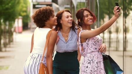 multiethnic : women with shopping bags taking selfie in city Stock Footage