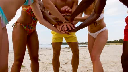 ingressou : happy friends stacking hands on summer beach
