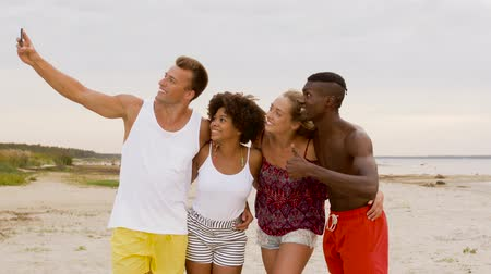 multiethnic : happy friends taking selfie on summer beach