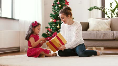 x mas : mother and daughter with christmas gift at home