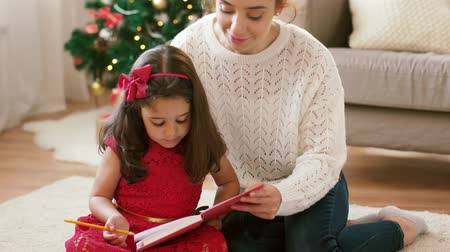 taslakkitabım : mother and daughter with notebook at christmas Stok Video